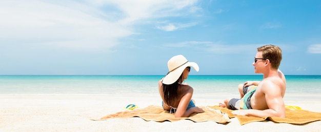 Par tumbado en la playa de arena blanca, relajarse y tomar el sol en las vacaciones de verano