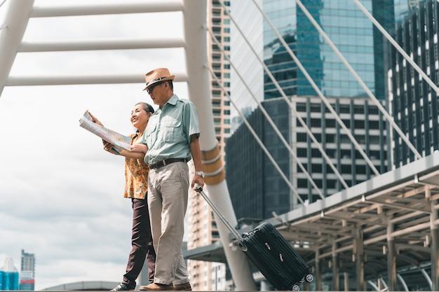 Un par de turistas asiáticos ancianos visitan la capital felices y divirtiéndose y mirando el mapa para encontrar lugares para visitar.