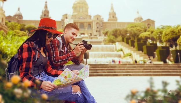 Un par de turistas estudian el mapa del templo antiguo. aventura de verano de joven y mujer.