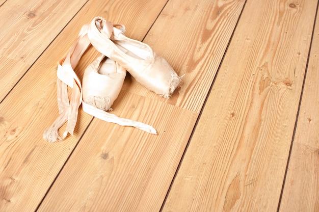 Par de viejas zapatillas de ballet en el piso de madera