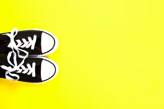 Par de zapatillas en blanco y negro sobre fondo amarillo brillante.