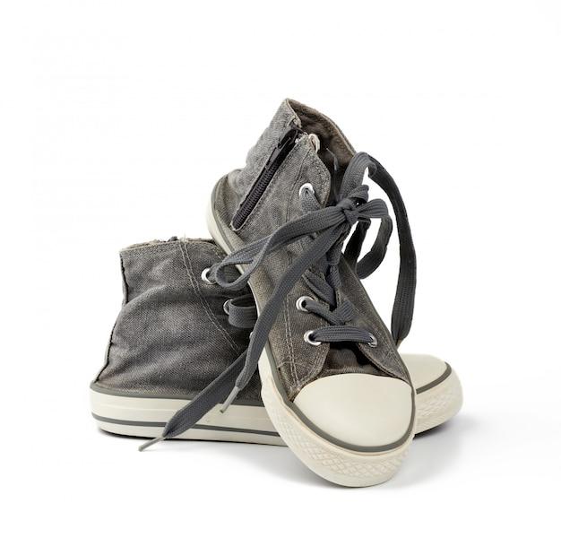 Par de zapatillas negras gastadas y gastadas con cordones blancos