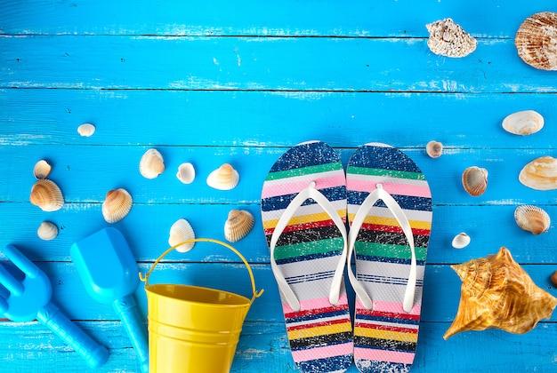 Par de zapatillas de playa femeninas, un cubo de bebé amarillo y conchas marinas dispersas