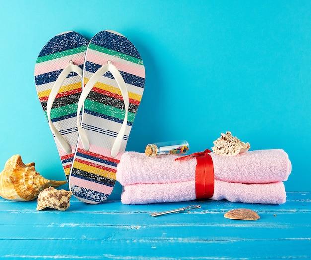 Par de zapatillas de playa femeninas y una toalla rosa sobre azul