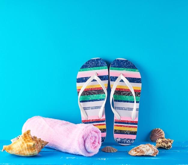 Par de zapatillas de playa femeninas y una toalla rosa sobre un fondo azul.