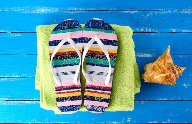 Par de zapatillas de playa femeninas y una toalla verde