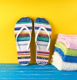 Par de zapatillas de playa femeninas y toallas sobre un fondo amarillo azul