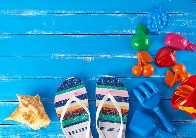 Par de zapatillas de playa a rayas femeninas, cubo de plástico rojo para bebés