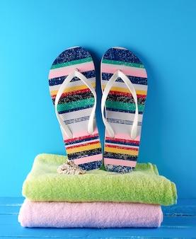 Par de zapatillas de playa y toallas.