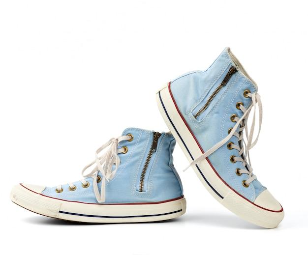 Par de zapatillas de tela desgastadas de color azul claro con cordones y cremalleras