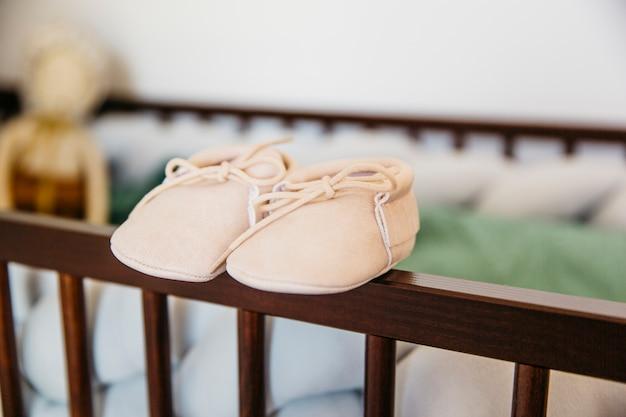 Par de zapatos de bebé en el borde de la cuna de madera.