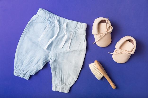 Par de zapatos de bebé; cepillo y pantalón del bebé sobre fondo azul