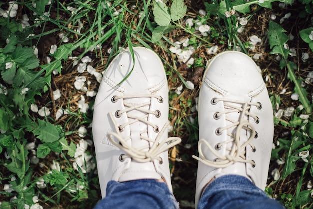 Par de zapatos blancos sobre hierba verde