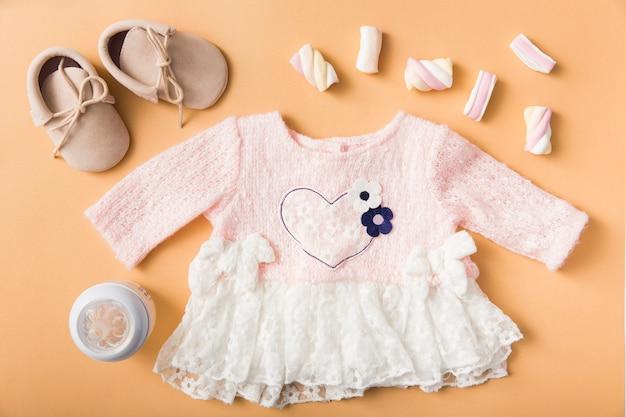 Par de zapatos; malvavisco; biberón y vestido rosa bebé sobre fondo naranja