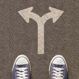 Par de zapatos de pie en una carretera con señal de tráfico
