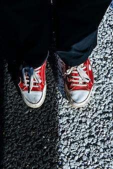 Par de zapatos rojos en el pavimento. textura de asfalto negro