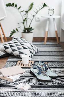 Par de zapatos transparentes de moda con libros, nota adhesiva y taza de café en la alfombra