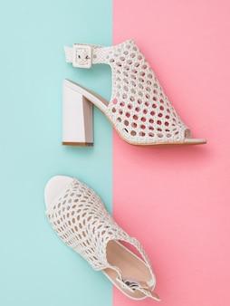 Un par de zapatos de verano de mujer hermosa en superficie azul y rosa. calzado de verano para mujer. endecha plana. la vista desde arriba.