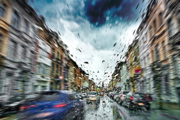 Parabrisas del coche con gotas de lluvia durante la tormenta y semáforos borrosos