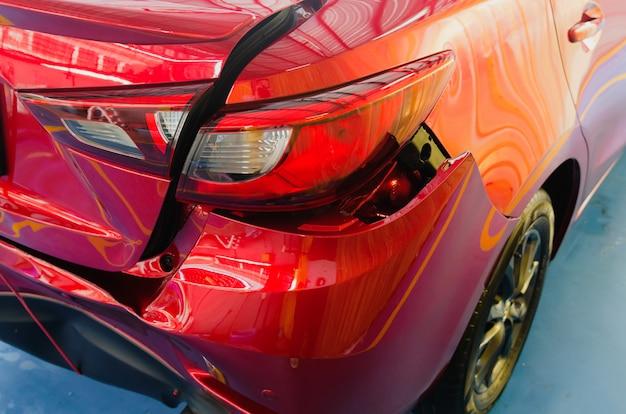 Parachoques trasero abollado coche rojo