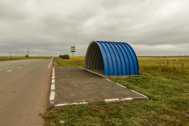 Parada de autobús azul vacía en la carretera