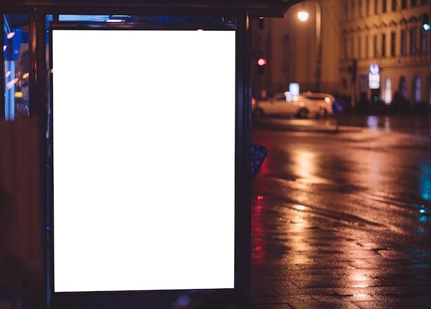 Parada de autobús durante la noche con espacio publicitario