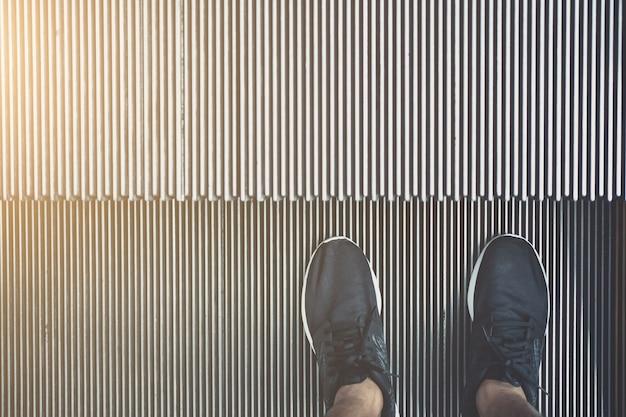 Parado humano en el proceso de escalera mecánica en tono de poca luz en estilo vintage