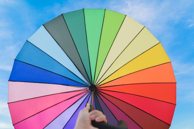 Paraguas de colores multicolor sobre un fondo de nubes de cielo azul