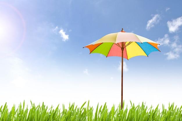 Paraguas colorido sobre fondo de naturaleza