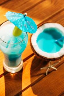 Paraguas decorado de vidrio y coco agrietado con bebida azul brillante.