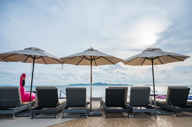 Paraguas con hamaca en piscina infinita en el mar tropical