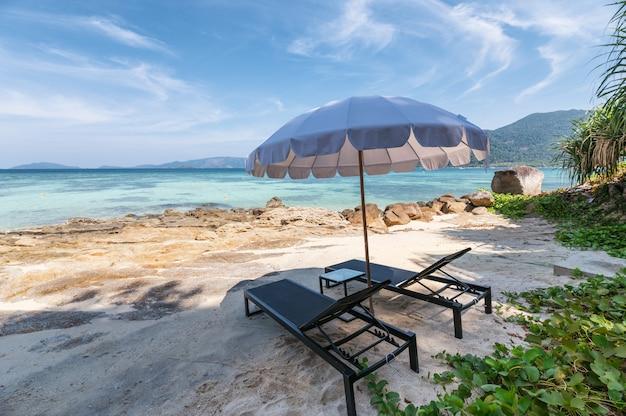 Paraguas con hamacas de madera en la playa blanca en el mar tropical