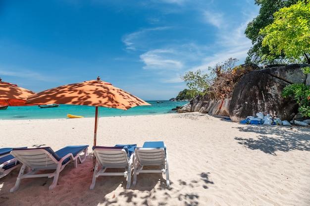 Paraguas con hamacas en la playa blanca en el mar tropical