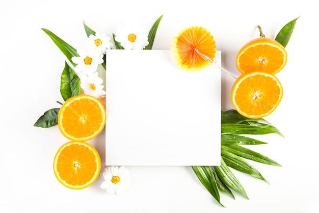 Paraguas y hoja de papel cerca de naranjas y flores