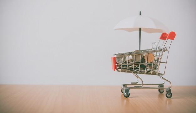 Paraguas está en la moneda, la moneda está en un carrito de compras que se coloca en el piso de madera. el concepto de protección y protección y supervisión de seguridad en los negocios.