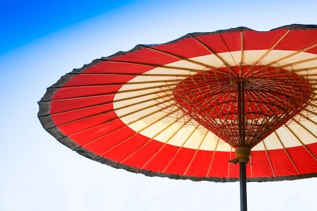 Paraguas de papel engrasado rojo y blanco chino tradicional sobre fondo de cielo azul