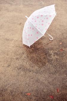 Un paraguas sobre suelo de cemento.