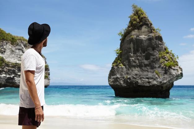 Paraíso en la tierra. hombre caucásico irreconocible en sombreros negros disfrutando de un lugar ideal en la orilla del océano con acantilados rocosos y agua turquesa que encontró durante su largo viaje a lo largo de la costa