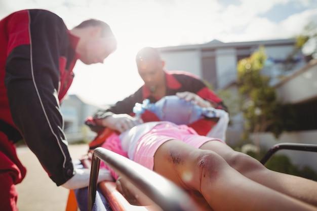 Paramédico dando oxígeno a una niña herida