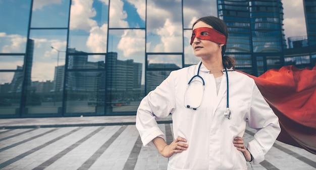 Paramédico femenino en un impermeable de superhéroe de pie en una calle de la ciudad. foto con espacio de copia.