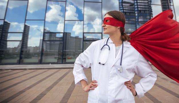 Paramédico femenino en un impermeable de superhéroe de pie en una calle de la ciudad