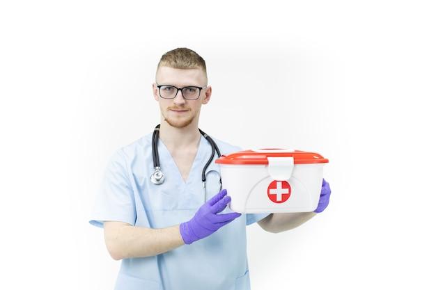 Paramédico en gafas y guantes de látex azul sostiene el caso médico de la cruz roja de cerca