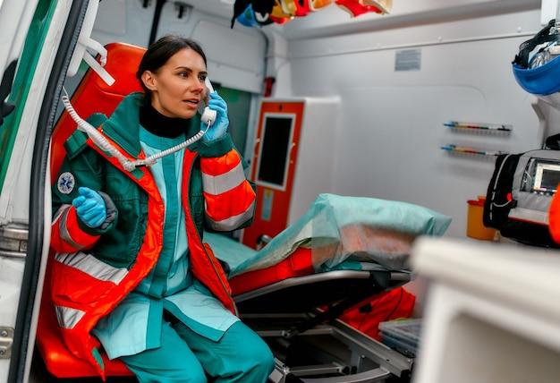 El paramédico de hermosa mujer en uniforme responde a la llamada telefónica mientras está sentado en una ambulancia moderna.