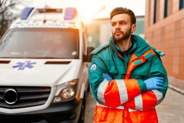 Un paramédico masculino guapo adulto se encuentra con los brazos cruzados frente a una ambulancia cerca de la clínica.