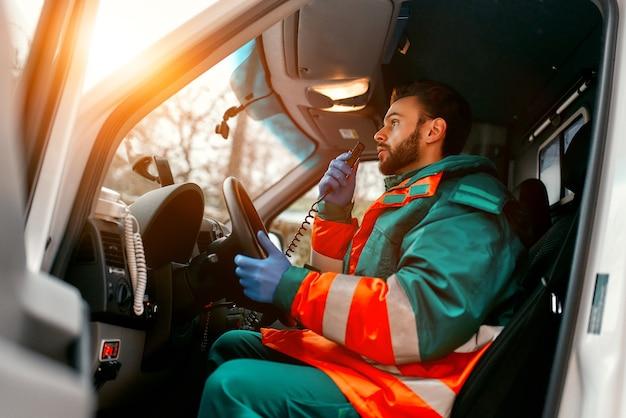 Un paramédico masculino guapo adulto está hablando por una radio portátil mientras está sentado en una ambulancia fuera de una clínica.