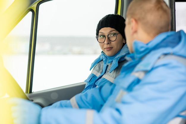 Paramédico de sexo femenino joven en uniforme y gorra hablando con el conductor del coche de la ambulancia mientras se apresura a salvar a la persona enferma