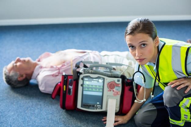 Paramédico utilizando un desfibrilador externo durante la reanimación cardiopulmonar