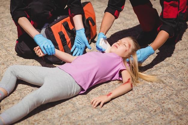 Paramédicos examinando niña herida