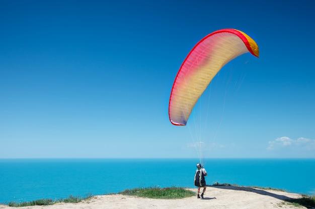 Parapente se prepara para el vuelo en un paraplane. fondo hermoso del verano.