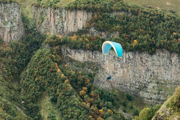 Parapente volar sobre la montaña en un día soleado. parapente en las montañas del cáucaso